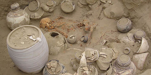 A skeleton surrounded with artifacts in a grave at the cemetery of the Burnt City 4